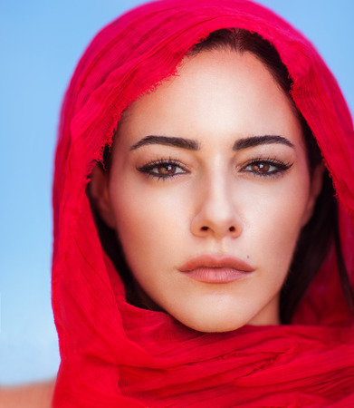 Photo for Closeup portrait of beautiful arabic woman wearing red headscarf over blue sky background, perfect natural makeup, traditional arabian beauty - Royalty Free Image