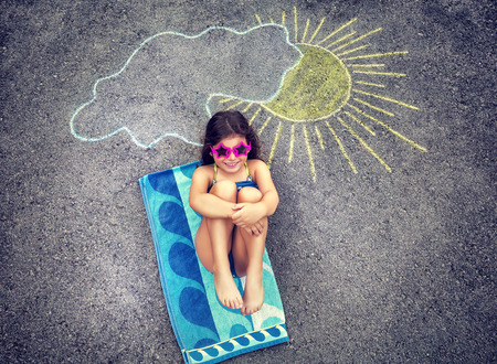 Foto de Cute creative little girl drawing on asphalt sun and tanning under it, wearing stylish swimsuit and sunglasses, summer holidays in the city - Imagen libre de derechos