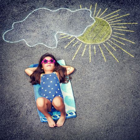 Photo pour Cute little baby girl having fun outdoors, drawing on asphalt sun and tanning under it, happy childhood in summer camp, active summertime holidays - image libre de droit