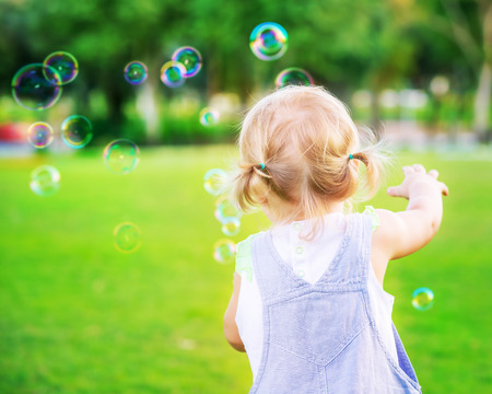 Photo pour Little baby girl try to catch soap bubbles, having fun outdoors, playing games in the park, happy carefree childhood - image libre de droit