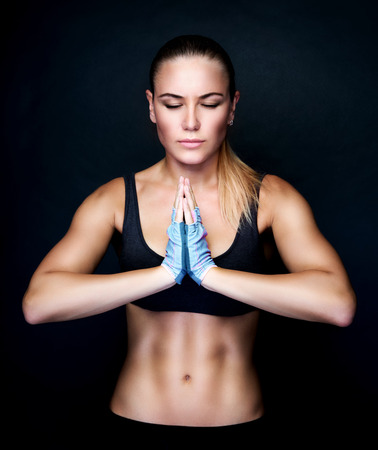 Foto de Beautiful woman meditating in the studio, doing yoga exercises over black background, sportive lifestyle, healthy active life - Imagen libre de derechos