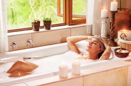 Foto de Woman relaxing at spa resort, lying down in the bath with closed eyes and make a compress, pleasure and healthy lifestyle - Imagen libre de derechos