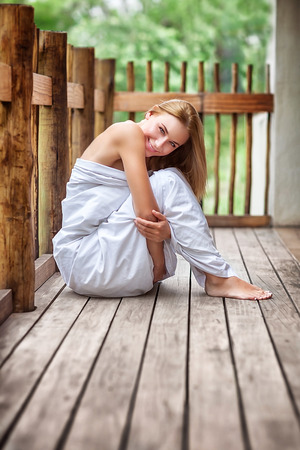 Gentle woman wrapped in the bed sheet sitting on the terrace, spending peaceful morning in spa hotel, relaxing outdoor and enjoying life