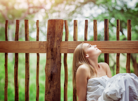 Sensual woman on spa resort, sitting on the floor of outdoors veranda wrapped in bed sheet and dreamy looking up on the sky, enjoying silence and nature harmony