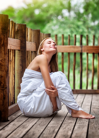 Sensual woman on spa resort, sitting on the floor of outdoors veranda wrapped in bed sheet, dreamy closing eyes and enjoying silence and harmony