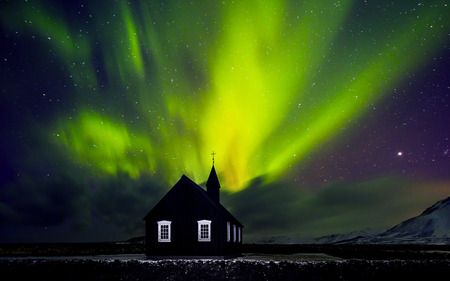 Photo for Beautiful bright green Northern light over church, little village in the Iceland, amazing forces of nature, wonderful night sky landscape - Royalty Free Image