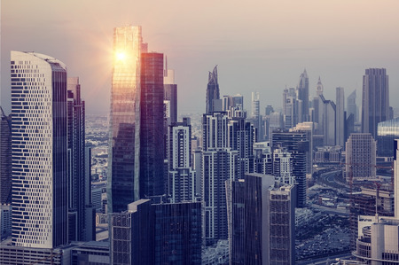 Foto de Dubai downtown in the evening, luxury modern buildings in bright yellow sunset light, futuristic cityscape, expensive life in UAE - Imagen libre de derechos