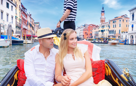 Photo pour Young happy couple riding on a gondola on Grand Canal in Venice, with pleasure spending honeymoon in Europe - image libre de droit