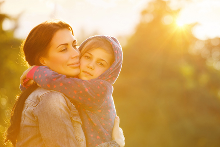 Photo for Portrait of beautiful mother with love hugging her precious daughter in bright yellow sunlight in the park, happy family life - Royalty Free Image