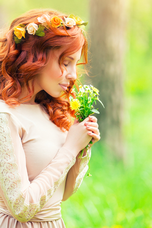 Foto de Portrait of a beautiful gentle woman in a forest, female enjoying aroma of a little bouquet of wild flowers, beauty of spring nature - Imagen libre de derechos