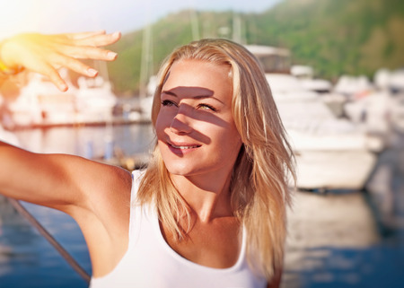 Photo for Portrait of a beautiful blond girl covering face by hand of bright sun light, spending weekend on the yacht, happy summer vacation - Royalty Free Image
