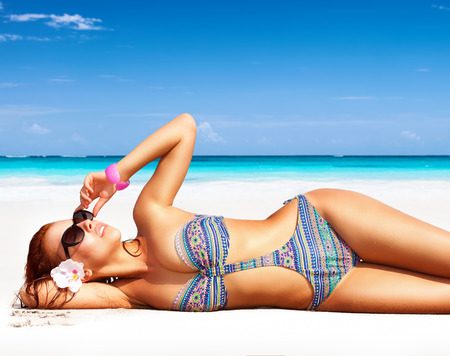 Foto de Beautiful woman on the beach, lying down on clean white sandy coast and with pleasure sunbathing, summer vacation on a tropical islands - Imagen libre de derechos