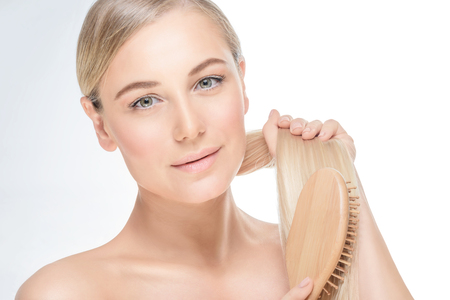 Photo pour Portrait of a gentle blond female combing her hair isolated on grey white background, treatment in spa salon, healthy hair and skin - image libre de droit