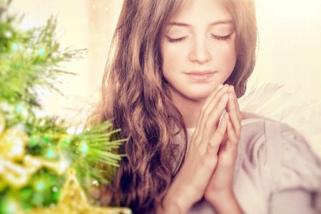 Photo for Closeup portrait of a beautiful calm girl with closed eyes praying near Christmas tree, gentle young angel wishing peace and harmony for everyone, happy religious holiday - Royalty Free Image