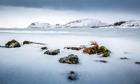 Foto de Beautiful winter landscape, amazing view on the frozen lake covered with white clean snow, cold but wonderful weather, Iceland, Scandinavia  - Imagen libre de derechos