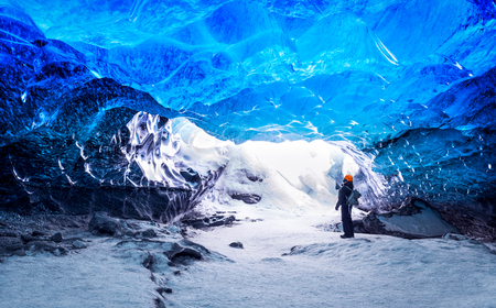 Photo pour Traveler in ice cave, man standing underground inside of a glacier, climate specific, Vatnajokull National Park, amazing nature of Skaftafell, Iceland - image libre de droit