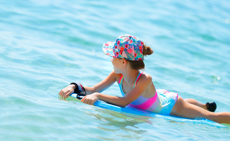 Photo pour Happy cheerful little girl swimming in the sea on a bodyboard, summertime activities, enjoying summer holidays on the beach resort - image libre de droit