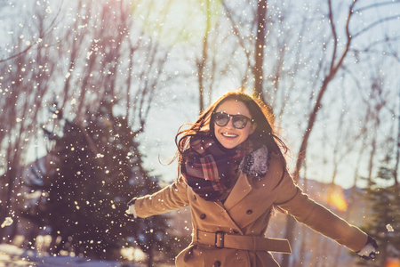 Photo pour Portrait of a pretty girl with pleasure spending time on bright sunny day in winter park, having fun like a child, happy wintertime vacation - image libre de droit