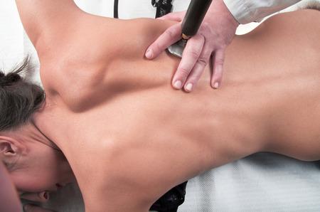 Foto de physical therapist massages the back of the girl with tecartherapy - Imagen libre de derechos