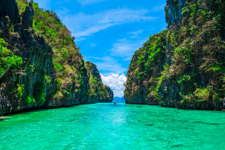 Foto de Tropical landscape with rock islands, lonely boat and crystal clear water, El Nido, Palawan, Philippines - Imagen libre de derechos