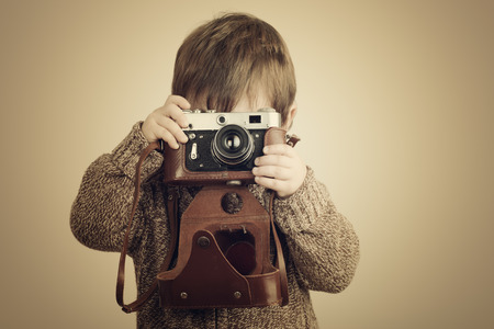 Photo for little boy taking pictures with old retro camera - Royalty Free Image