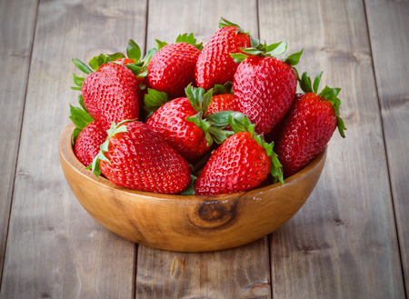 Photo for a bunch of ripe strawberries in a wooden bowl on the table - Royalty Free Image