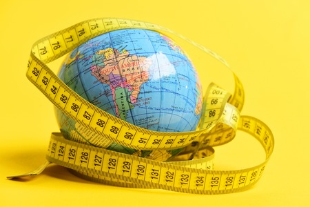 Photo for Concept of long distant travel: globe wrapped around with measuring tape isolated on bright yellow background - Royalty Free Image