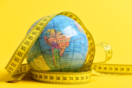 Photo pour Earth globe wrapped around with measuring tape isolated on bright yellow background. Symbol of worldwide food issue - image libre de droit