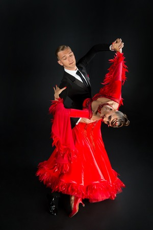 Photo pour dance ballroom couple in red dress dance pose isolated on black background. sensual professional dancers dancing walz, tango, slowfox and quickstep. - image libre de droit