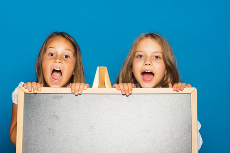 Photo for Children with opened mouths, copy space. Girls in school uniform on blue background. Education and school concept. Schoolgirls with surprised faces stand near blackboard. - Royalty Free Image