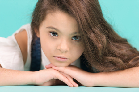 Photo pour Little girl with long brunette hair pose. Small model with adorable face skin on blue background. Skincare, beauty, look, hairstyle. Child, childhood, preteen, youth, punchy pastel - image libre de droit