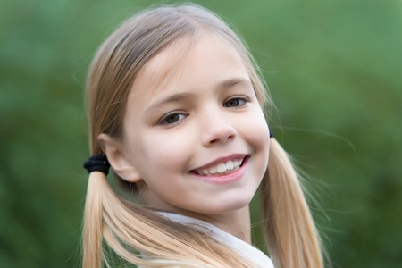 Photo pour Little girl smile on natural background, childhood. Child with blond hair ponytails smiling outdoor. Happy childhood concept. Beauty, look, hairstyle. - image libre de droit