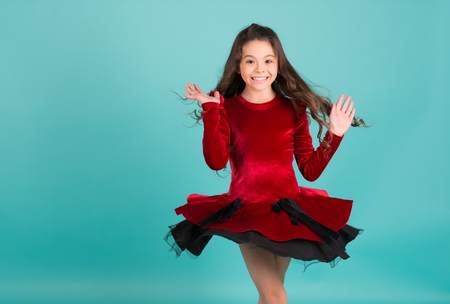Photo pour Girl dancer spin in red dress blue background. Happy child smile with long brunette hair. Performance, ballet, activity, energy concept. Grace, beauty, fashion, copy space - image libre de droit