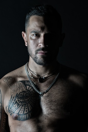 Photo pour Bearded man with tattooed chest. Macho with sexy bare torso. Fit model with tattoo art on skin. Sportsman or athlete with stylish beard and hair. Sport and fitness. Confidence and masculinity. - image libre de droit