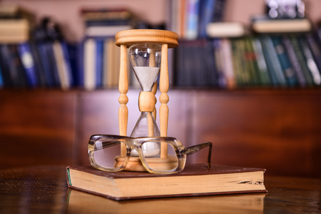 Photo for Librarian attributes concept. Hourglass counting time near old fashioned eyeglasses. Sand falling down inside of hourglass. Hourglass, old book and eyeglasses on wooden table, library on background - Royalty Free Image