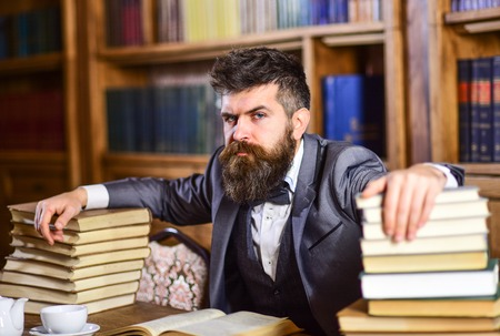 Photo for Man sits at table with many books. - Royalty Free Image