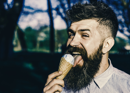 Photo for Funny tourist. Man with long beard licks ice cream, close up. Bearded man with ice cream cone. Man with beard and mustache on happy face eats ice cream, nature background, defocused. Chilling concept - Royalty Free Image