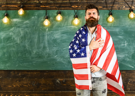 Photo pour Patriotic education concept. American teacher covered with american flag. Man with beard and mustache on serious face with flag of USA, chalkboard on background. Teacher teaches to love homeland, USA - image libre de droit