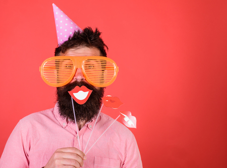 Photo for Guy in party hat celebrate, posing with photo props. Hipster in giant sunglasses celebrating. Man with beard on cheerful face holds smiling lips on sticks, red background. Emotional diversity concept - Royalty Free Image