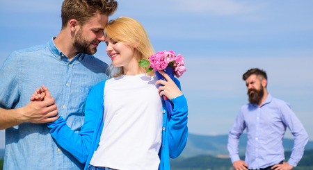Photo for Ex partner watching girl starts happy love relations. New love. Couple in love dating outdoor sunny day, sky background. Ex husband jealous on background. Couple with flowers bouquet romantic date - Royalty Free Image