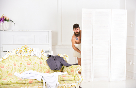 Photo for Hipster naked on shocked face unexpectedly detected in bedroom. Exposing lovers concept. Man with beard and mustache hiding behind folding screen. Man, lover in white interior caught naked - Royalty Free Image