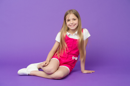 Photo pour Happy girl relax on violet background. Beauty and fashion look. Little child with smile on cute face, beauty. Fashion kid smiling with long blond hair. So young and so stylish. Cute and fashionable - image libre de droit