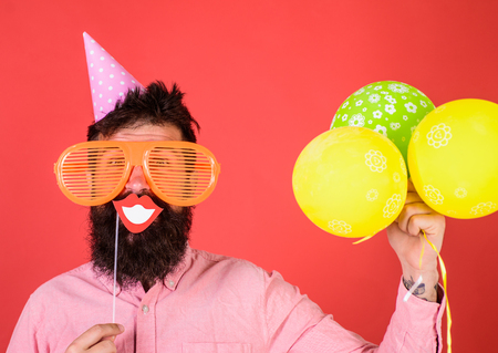 Photo for Hipster in giant sunglasses celebrating. Guy in party hat with air balloons celebrates. Photo booth fun concept. Man with beard on cheerful face holds smiling mouth on stick, red background - Royalty Free Image