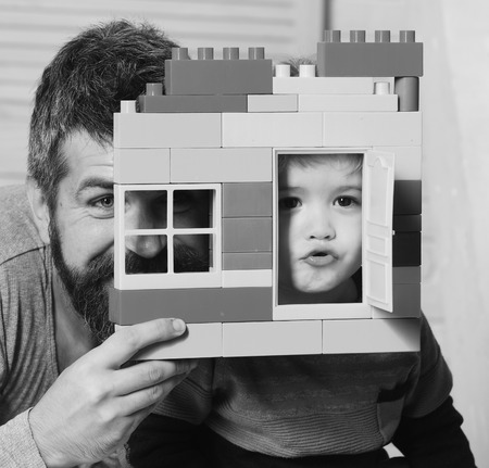 Dad and kid hide behind house made of colored blocks. Boy and bearded man play together. Family game and childhood concept. Father and son make grimaces looking through window of toy construction.