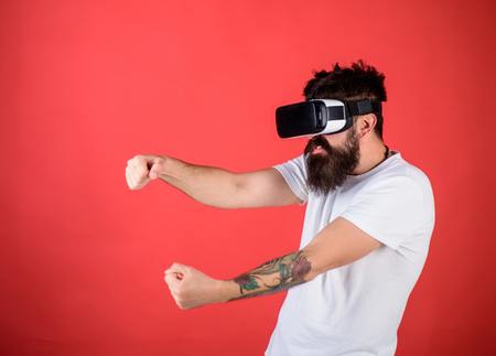 Photo pour Man with beard in VR glasses driving car, red background. Virtual racing concept. Guy play racing game in VR. Hipster on aggressive face driving car on high speed in virtual reality. - image libre de droit