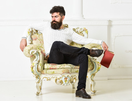 Foto de Man with beard and mustache sits on armchair, holds book, white wall background. Connoisseur on thoughtful face finished reading book. Guy thinking about literature. Reflections on literature concept. - Imagen libre de derechos