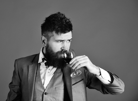 Foto de Connoisseur with serious face tasting expensive cabernet wine. Sommelier with beard on red background. Degustation and winetasting concept. Man in suit drinking sparkling glass of red wine. - Imagen libre de derechos