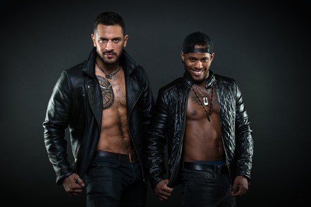 Foto de Bodybuilders with bare torsos. Cheerful African man with broad smile wearing cap. Brutal Caucasian man with tattoo on hairy chest. Bikers in leather jackets on muscular body, masculinity concept. - Imagen libre de derechos