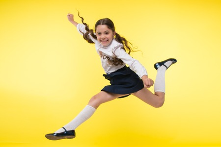Foto de Toward knowledge. Girl make supernatural efforts on way to knowledge. Thirst of knowledge. Back to school. Kid cheerful schoolgirl full of energy jump in mid air. Pupil want study. Lets begin study. - Imagen libre de derechos