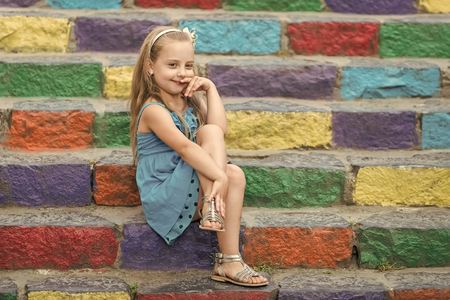 Foto de small baby girl or cute child with adorable smiling face and bow in blonde hair in blue dress outdoor sitting on colorful stony stairs background, copy space - Imagen libre de derechos